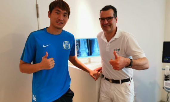 Fußballspieler Rui steht Li mit Dr. Simon im Behandlungsraum